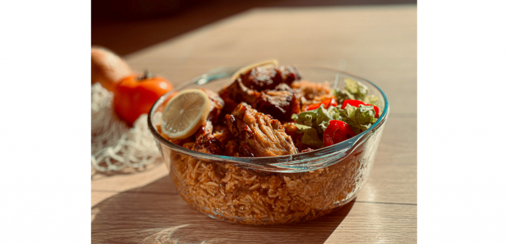 A plate of delicious jollof rice with loaded meat and salad